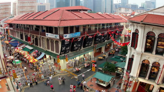 Time lapse high angle shot of busy shopping complex and outdoor market stalls in Chinatown from day to dusk / Singapore
