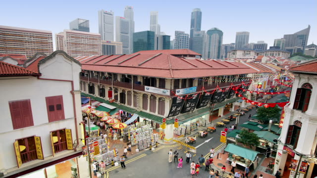 Time lapse high angle shot of busy shopping complex and outdoor market stalls in Chinatown with view of Singapore skyline in background