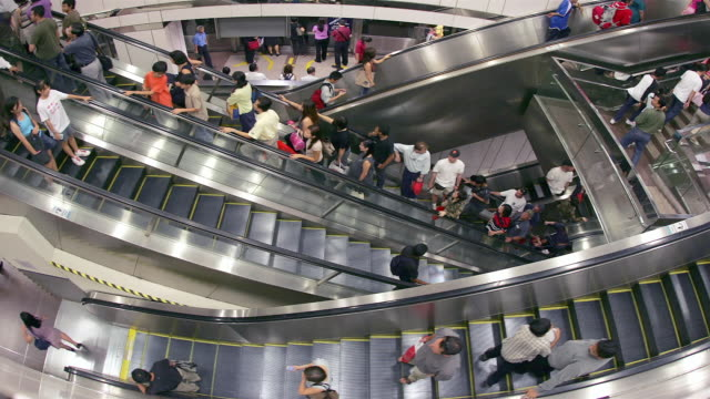 time lapse high angle shot of commuters riding escalators in mass rapid transit station / singapore - rolltreppe stock-videos und b-roll-filmmaterial