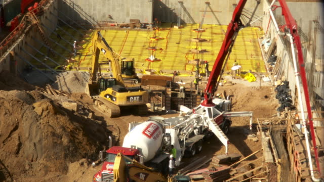 Time lapse high angle shot of construction site and cement truck.