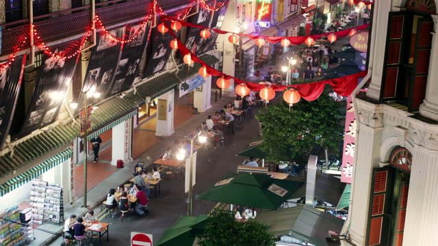 Time lapse high angle shot of people walking under lanterns strung over street market in Chinatown at night / Singapore