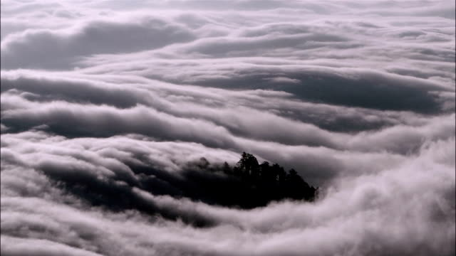 time lapse high angle wide shot fog rolling in off the pacific ocean / california - north pacific stock videos & royalty-free footage