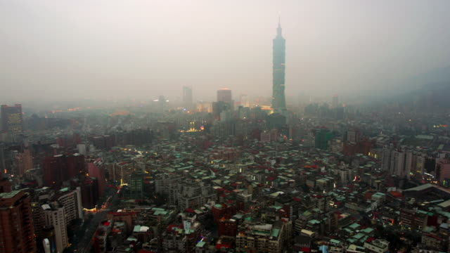 Time lapse high angle wide shot of Taipei 101 and the city of Taipei through the mist / day to night / Taipei City, Taiwan