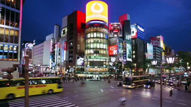 time lapse high angle wide shot pedestrians and traffic at ginza crossing with san-ai building in background at night / tokyo, japan - ginza stock videos & royalty-free footage