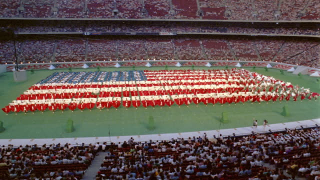 1986 time lapse high angle wide shot performers in US flag formation on field during Liberty Weekend at Giants Stadium /NJ