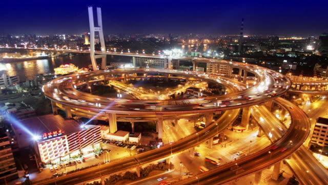 time lapse high angle wide shot traffic on nanpu bridge spiral at night / shanghai - 螺旋形点の映像素材/bロール