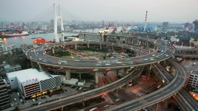 time lapse high angle wide shot traffic on nanpu bridge spiral / day to night / shanghai - 螺旋形点の映像素材/bロール