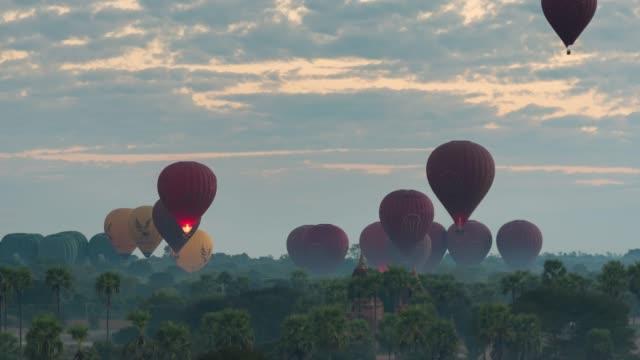 vídeos de stock, filmes e b-roll de lapso de tempo de 4k: hot balões voando sobre templos de bagan, antigo pagode em mianmar bagan - templo