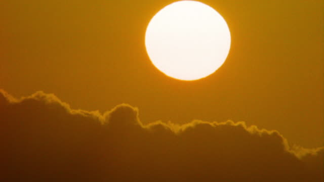 time lapse huge sun setting behind BACKLIT clouds moving in darkening sky