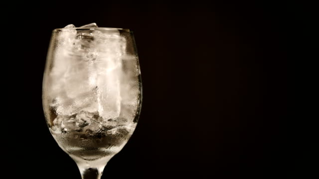 zeit ablauf eis im wasserglas schmelze auf schwarzem hintergrund - getränk stock-videos und b-roll-filmmaterial