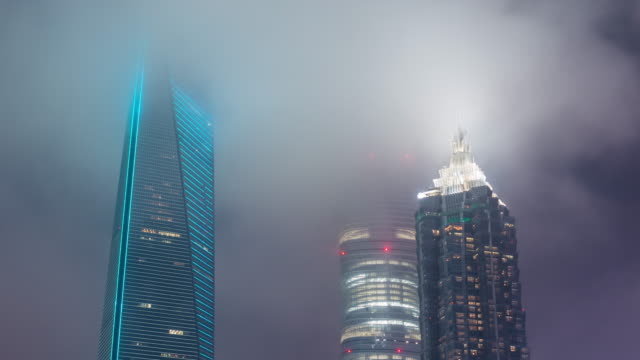 time lapse- illuminated skyscrapers in shanghai at night in foggy weather (cu la panning) - shanghai stock videos & royalty-free footage