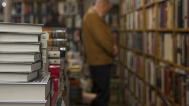 time lapse in bookshop moving past stacks of books - choosing stock videos & royalty-free footage