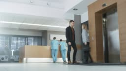 Time Lapse in the Hospital. Doctors, Nurses, Assistant Personnel and Patients Working and Walking in the Lobby of the Medical Facility.