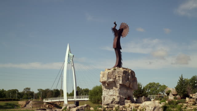 "vídeos de stock e filmes b-roll de time lapse ""keeper of the plains"" native american statue and pedestrian walking bridge, with blue sky and white clouds - kansas"