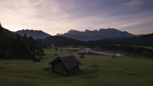 time lapse. lake geroldsee with hay barns and karwendel mountains in background at sunrise. geroldsee, mittenwald, garmisch-partenkirchen, bavarian alps, karwendel mountains, bavaria, germany. - karwendel mountains stock videos and b-roll footage