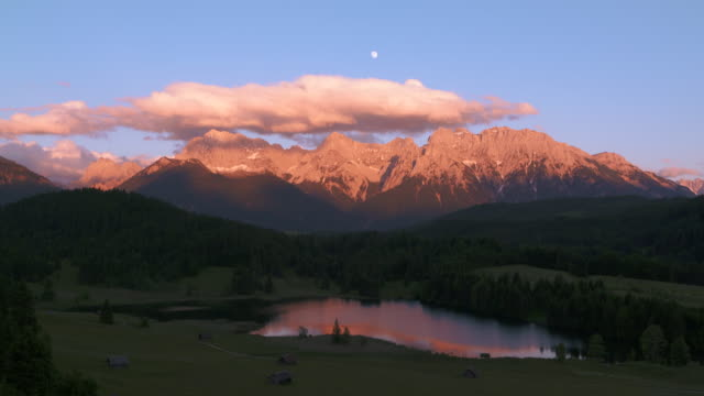 time lapse. lake geroldsee with huts and karwendel mountains in background at full moon, sunset. - karwendel mountains stock videos and b-roll footage