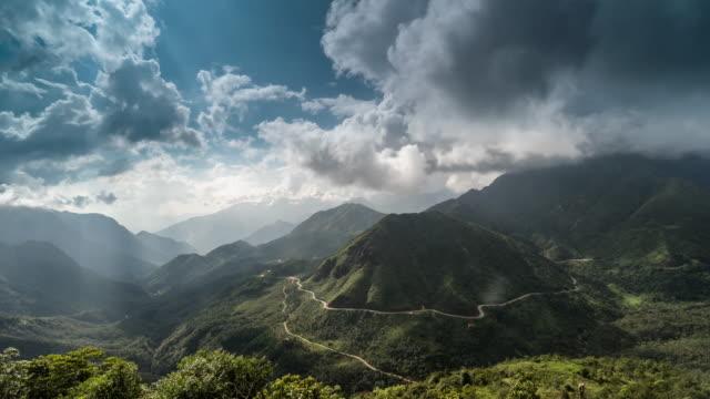 Tijd lapse landschap fantastische schot van de beklimming van de bergketen.  Bewolkte hemel en straal van de zon boven de Misty heuvel weg in de bergen van de hoge rots