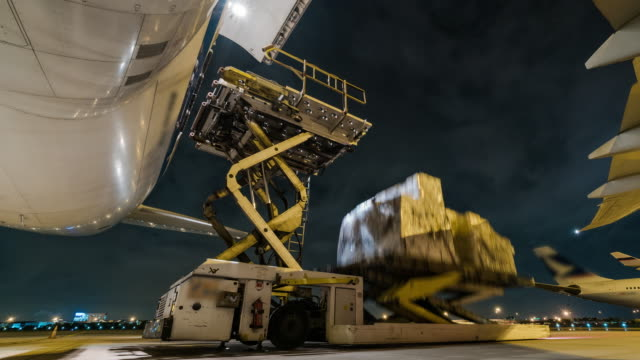 Time lapse loading cargo outside cargo plane at night