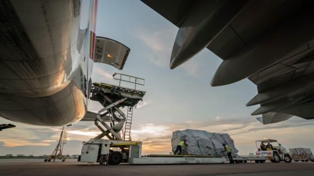 zeitraffer laden frachtflugzeug mit sonnenuntergang - loading stock-videos und b-roll-filmmaterial