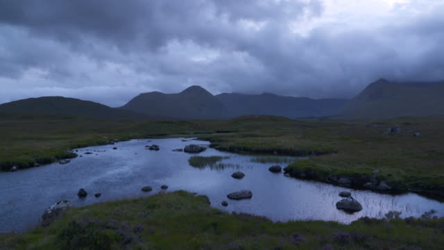Time Lapse. Loch Bá in Rannoch Moor with dark rain clouds. Loch Ba, Rannoch Moor, Glencoe, Highlands, Scotland, UK.