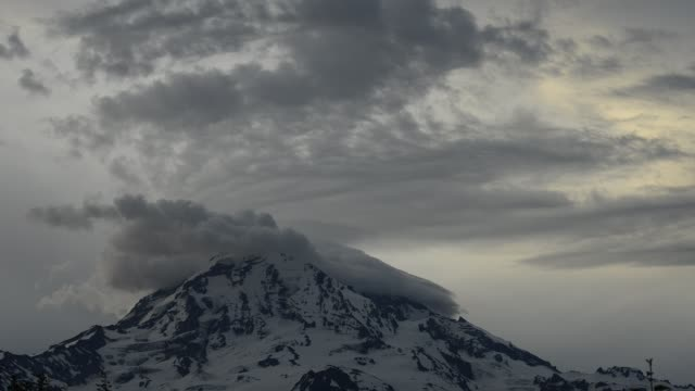 time lapse lockdown shot of cloudscape over snow covered mountain at mount rainier national park - mt rainier national park stock videos & royalty-free footage