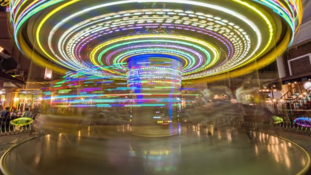 4K Time lapse long exposure of Carousel amusement ride with horses rotating circular platform with seats for riders in fun park, Entertainment and Merry-go-round concept