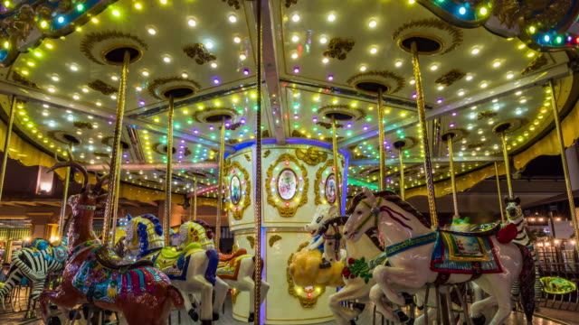 4k time lapse long exposure of carousel amusement ride with horses rotating circular platform with seats for riders in fun park, entertainment and merry-go-round concept - circus stock videos & royalty-free footage
