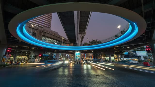 time lapse long exposure of traffic jam and car crowd intersection in rush hour at night time in bangkok, transportation with cityscape concept - futuristico video stock e b–roll