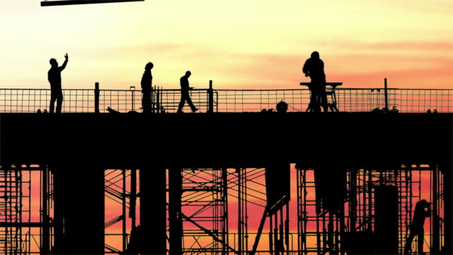 Time lapse long shot dolly shot silhouettes of construction workers working on scaffolding at sunset / Mississauga, Canada