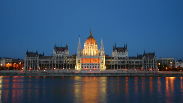 Time lapse long shot dome of Parliament lit up at twilight / boats passing on Danube in foreground / Budapest, Hungary