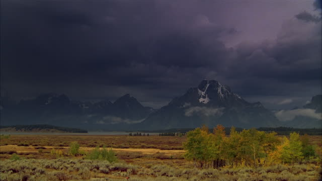 time lapse long shot low, dense clouds passing over rocky mountains and field at yellowstone national park / wyoming - yellowstone national park stock videos & royalty-free footage
