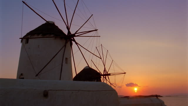 time lapse long shot motionless windmills with sun setting in background / dusk / mykonos, greece - mykonos stock videos & royalty-free footage