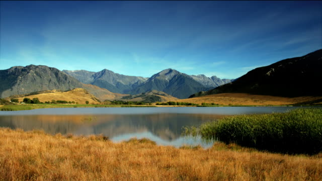 Time lapse long shot Mount Horrible and Lake Sarah with reflection of mountain in lake / Canterbury, New Zealand