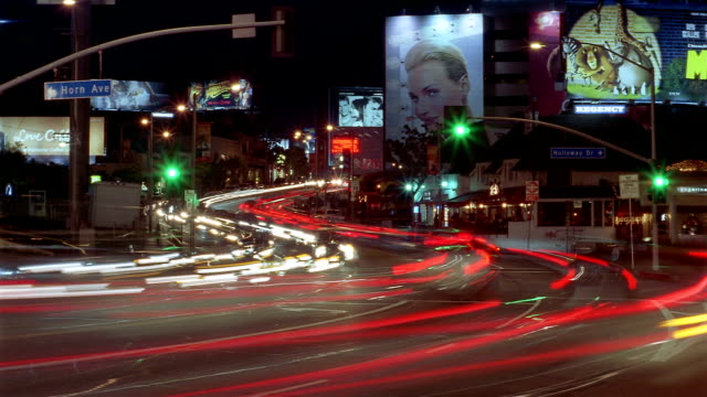 time lapse long shot traffic stopping and going at stoplight on sunset boulevard at night / los angeles, california - sunset boulevard stock-videos und b-roll-filmmaterial