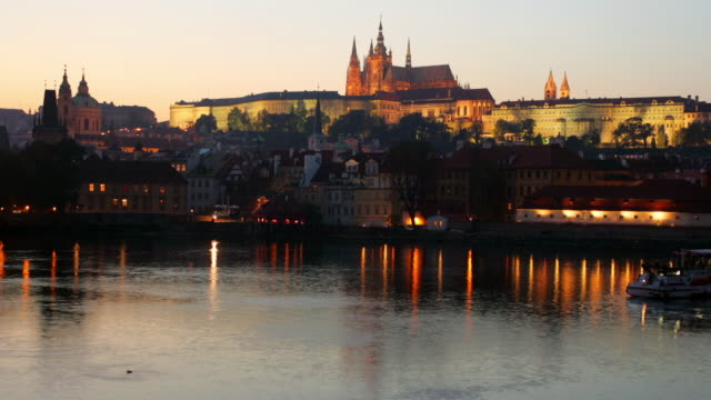 time lapse long shot view of hradcany castle / boats passing on vltava in foreground / prague, czech republic - hradcany castle stock videos and b-roll footage