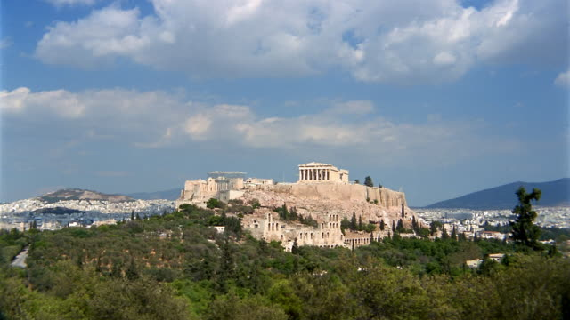 Time lapse long shot view of Parthenon on Acropolis from Filopappos Hill / clouds rolling in blue sky / Athens
