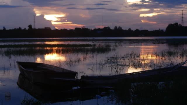vidéos et rushes de bateau longtail laps de temps sur le lac au coucher du soleil - lancer la ligne de canne à pêche
