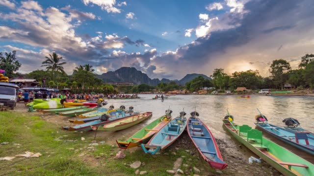4k time lapse : longtail boats and tourist paddle kayak boat travelling on nam song river in vang vieng, laos. - wide stock videos and b-roll footage