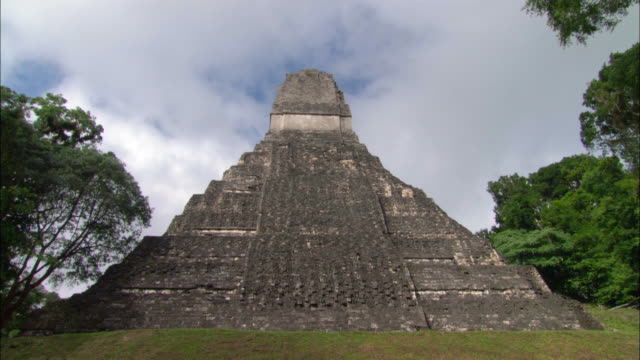 time lapse low angle long shot of the temple of the grand jaguar at the great plaza mayan ruins / tikal, guatemala - mayan stock videos and b-roll footage