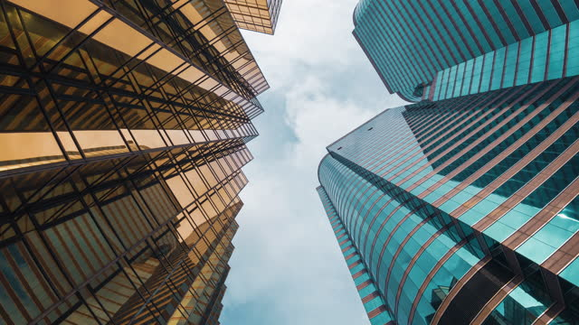 time lapse low angle of tall corporate buildings skyscraper in hong kong - low angle view stock videos & royalty-free footage