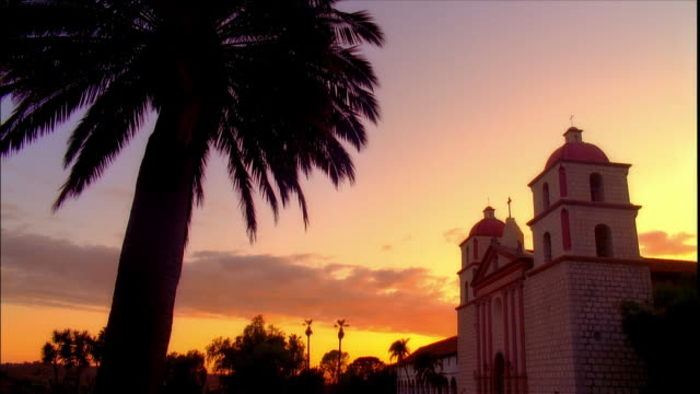 Time lapse low angle view of palm tree and Mission Santa Barbara with clouds passing overhead / Santa Barbara, California