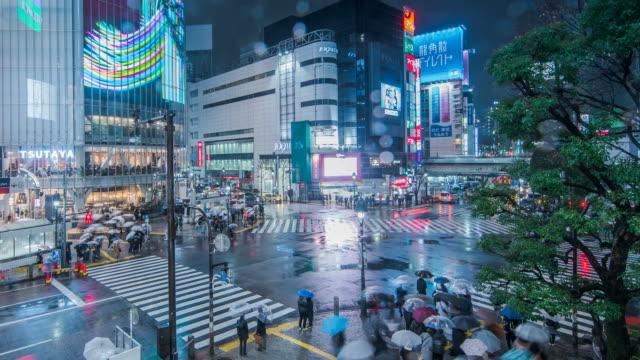 vídeos de stock e filmes b-roll de time lapse low angle view of pedestrians on shinjuku-dori avenue in east shinjuku on rainy night / tokyo, japan - parede de vídeo