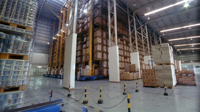 Time lapse low angle wide shot boxes being moved around on robotic pallets in warehouse at milk factory /