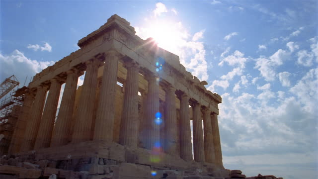 time lapse low angle wide shot clouds rolling over parthenon / sun shining overhead / athens, greece - parthenon athens stock videos and b-roll footage