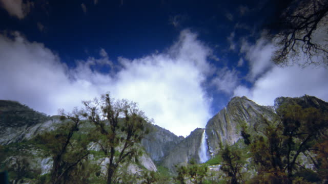 time lapse low angle wide shot pan trees / mountains/ waterfall with clouds in sky / yosemite national park, california - yosemite national park stock videos and b-roll footage