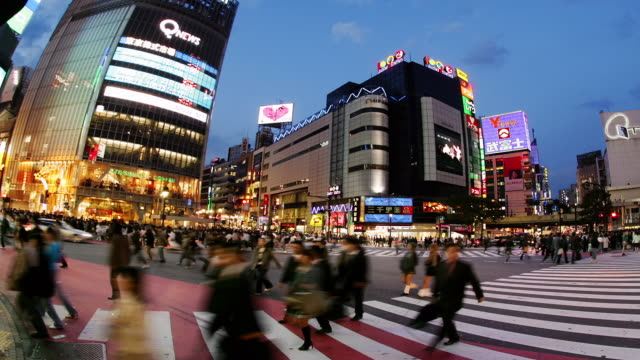 time lapse low angle wide shot pedestrians and traffic across shibuya crossing with 109-2 bldg in background / night / tokyo, japan - bildschirmwand stock-videos und b-roll-filmmaterial