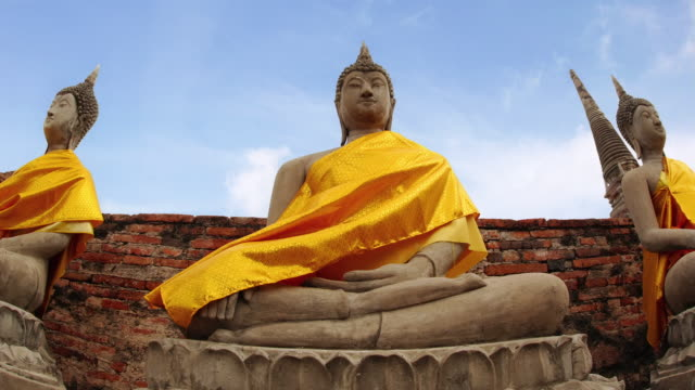 Time lapse low angle wide shot seated buddha  outside the chedi at Wat Yai Chai Mongkol (Wat Phra Chao Phya-thai) temple / Bangkok, Thailand