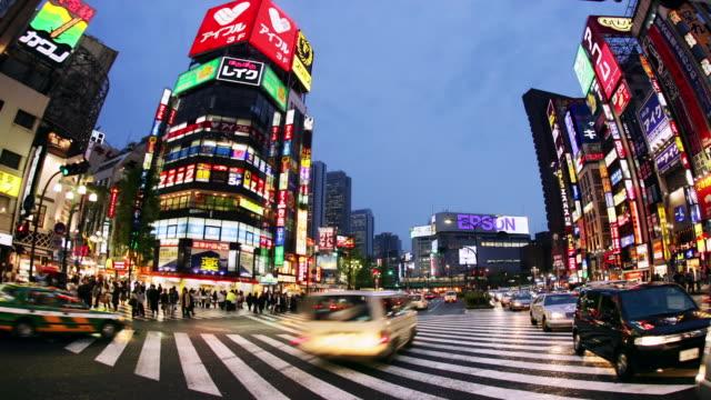 time lapse low angle wide shot traffic and pedestrians at east shinjuku crossing / tokyo, japan - 広角撮影点の映像素材/bロール