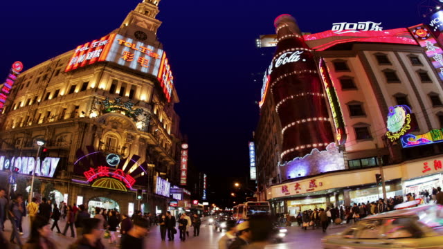 time lapse low angle wide shot traffic passing large neon coke bottle on building on nanjing road at night / shanghai - wide angle stock videos & royalty-free footage