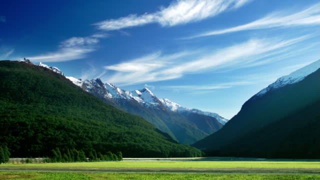 vidéos et rushes de time lapse low angle wide shot view of clouds over valley in mt aspiring national park from haast / south island, nz - mont aspiring